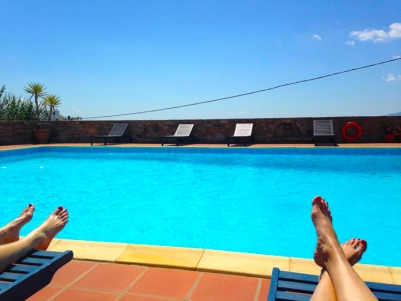 A blue swimming pool and blue sky with lounge chairs on a sunny day.